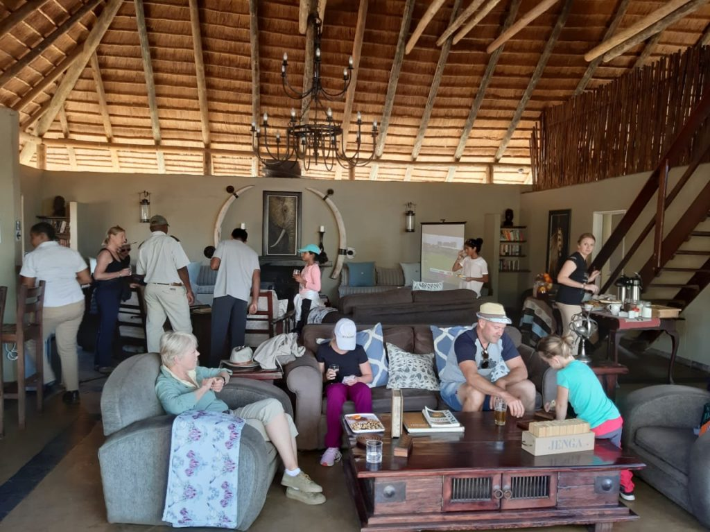 Guests relaxing together and watching the world cup cricket final at safari lodge